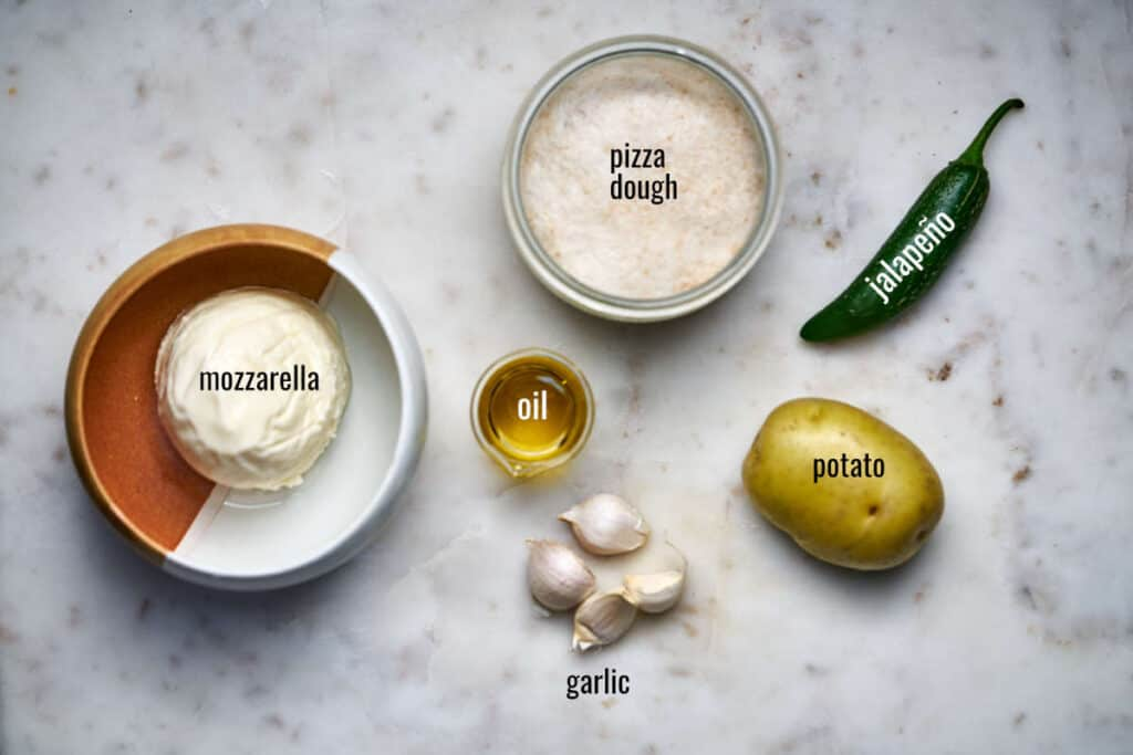 Ingredients for potato jalapeño pizza including mozzarella, pizza dough, and garlic.