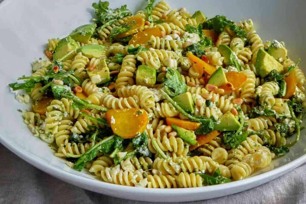A full serving bowl of fussili pasta salad with greens, beets, and avocado.