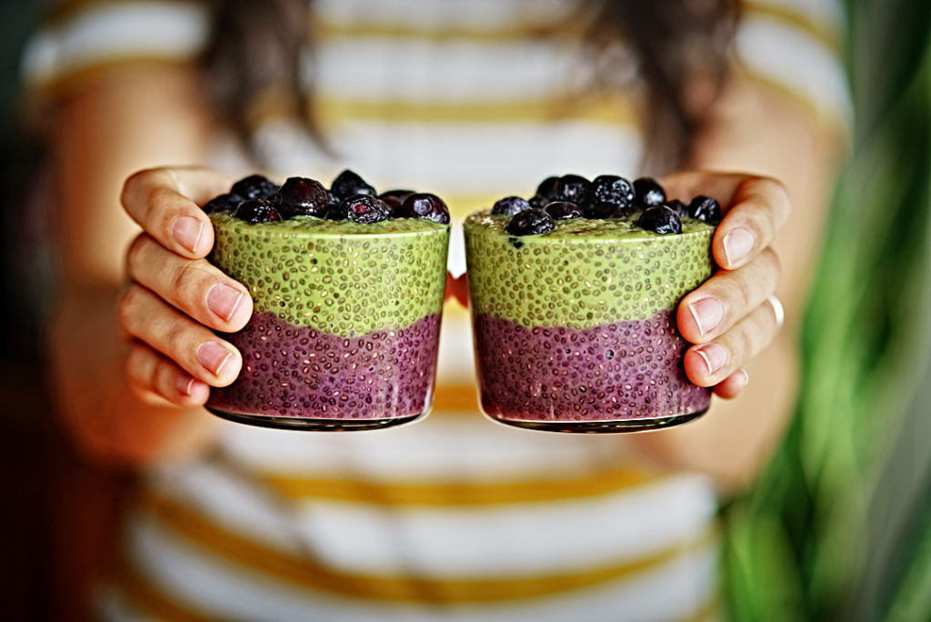 Girl holding layered chia pudding with green and purple chia pudding.