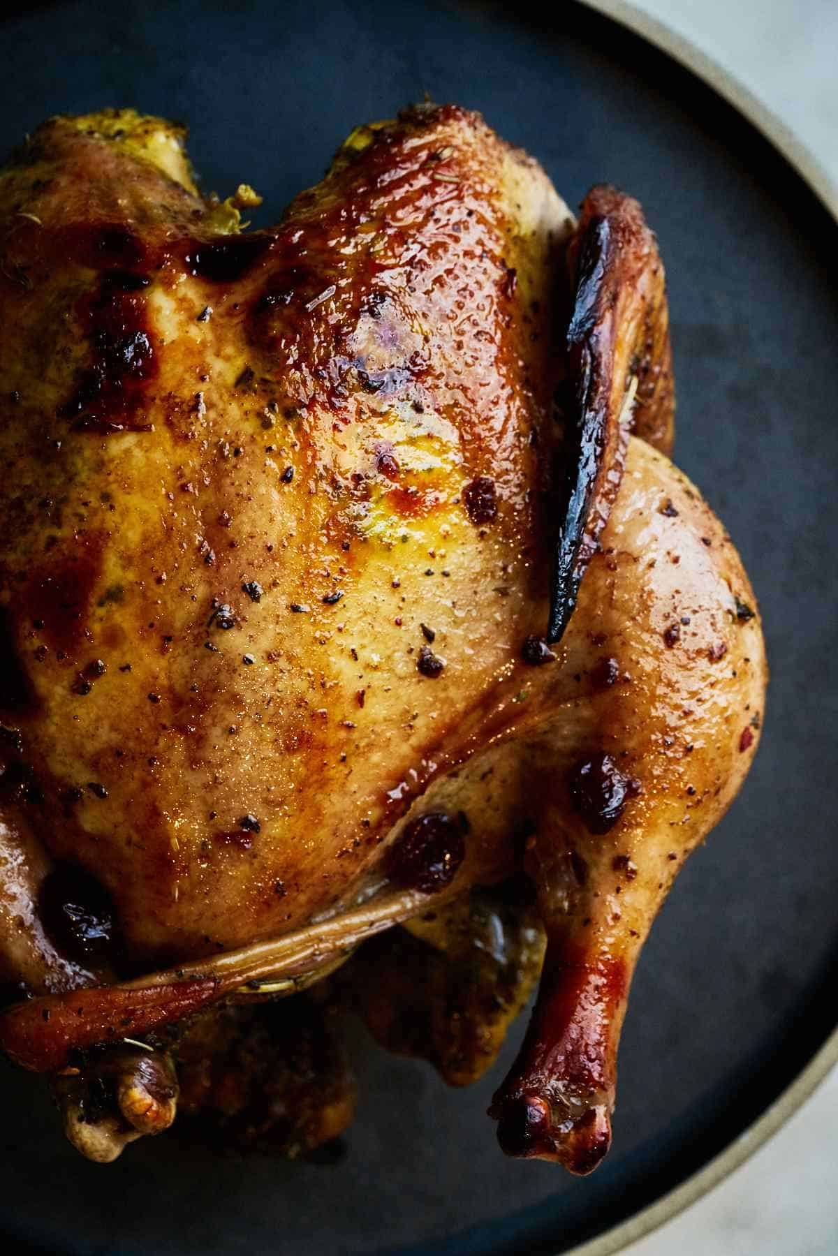 Roasted whole chicken on a black plate.