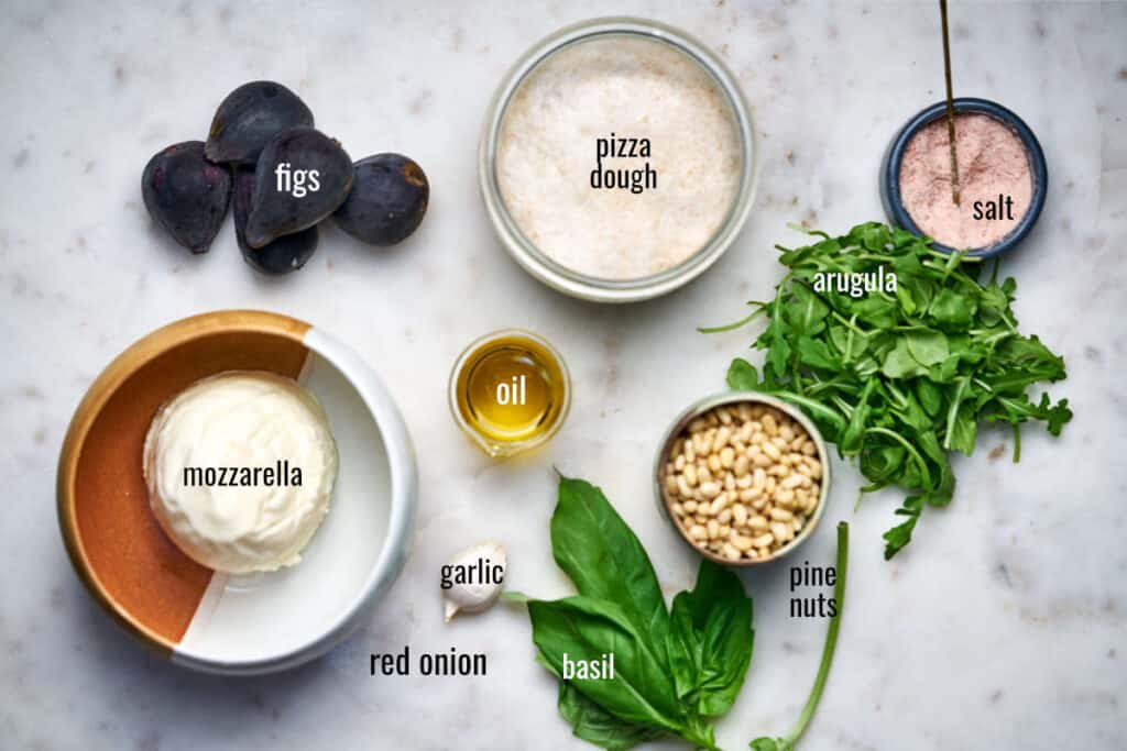Ingredients for fig pizza including pesto ingredients and arugula.