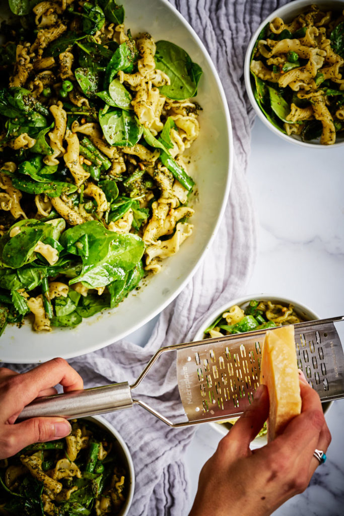 Shaving parmesan cheese over green pasta salad.