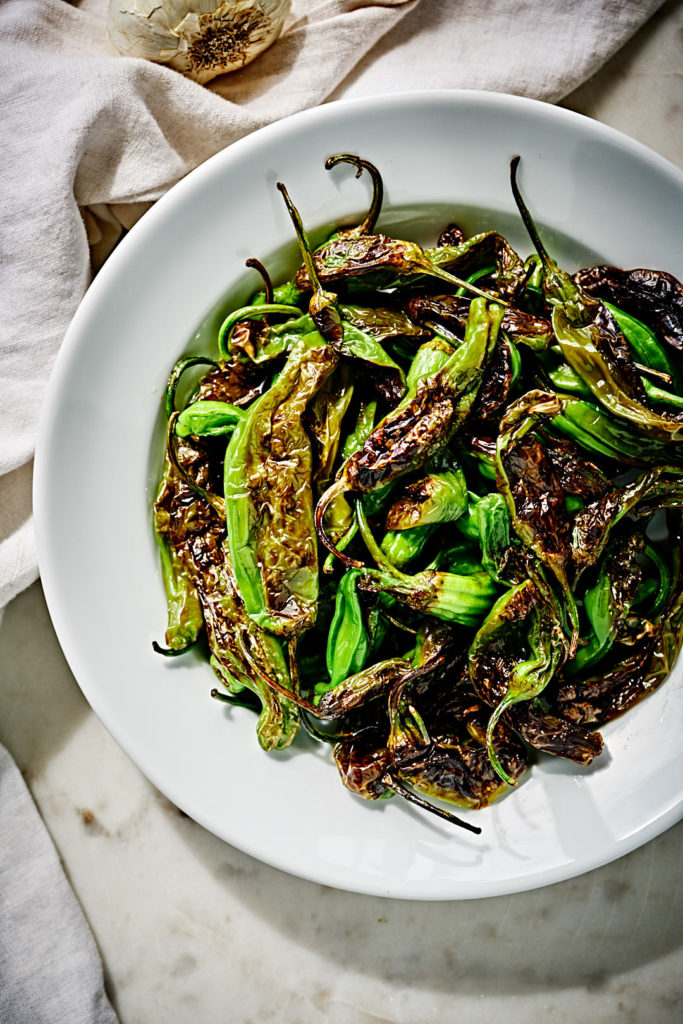 Blistered shishito peppers in a white plate.