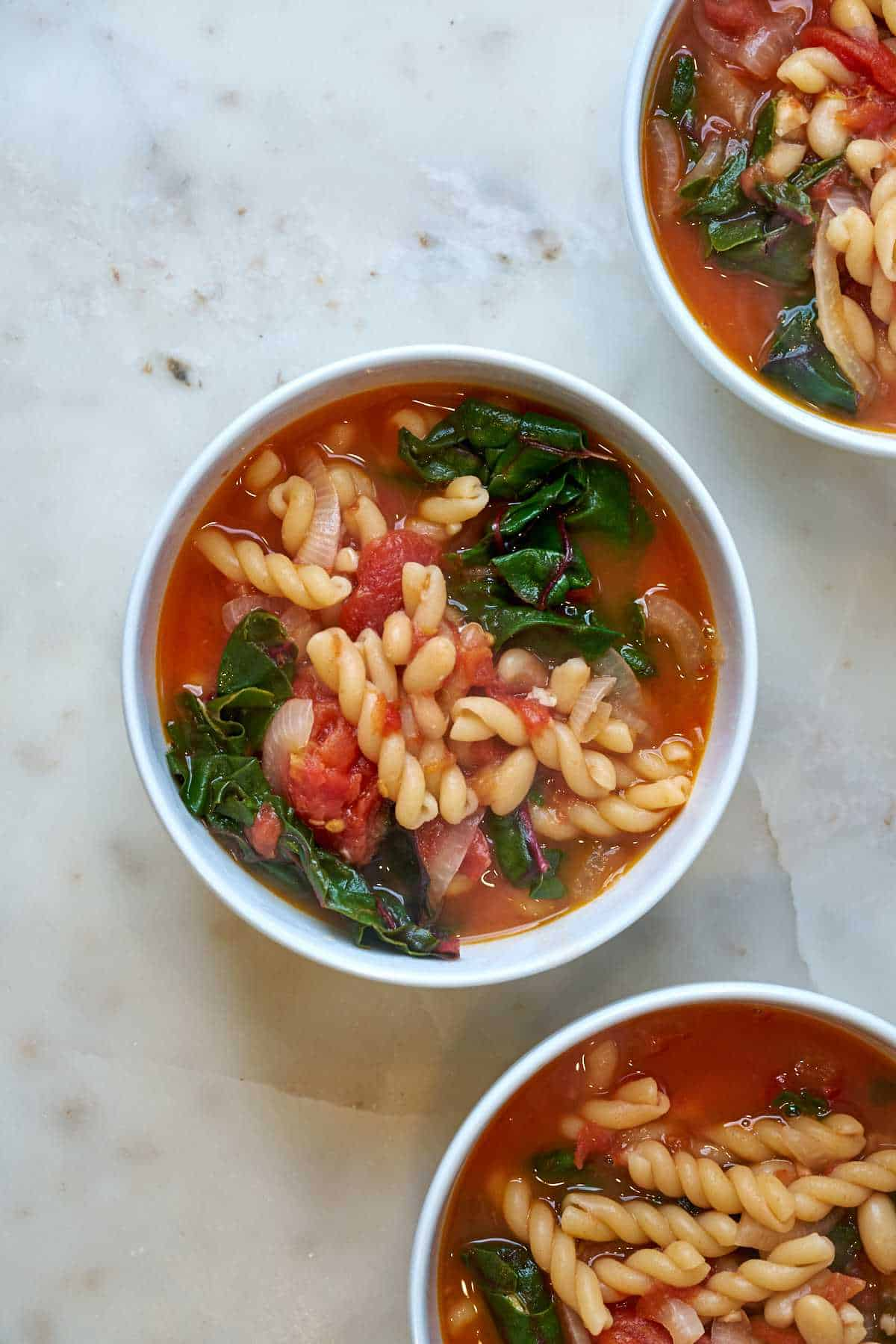 Three bowls of Bowl of red soup with noodles and greens.