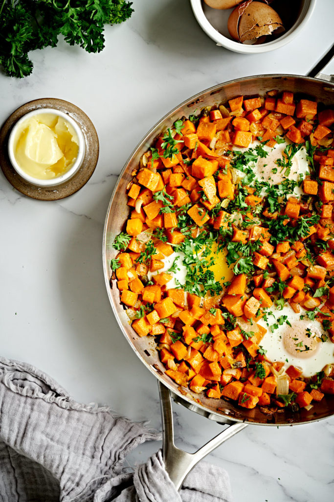 Sweet potato hash in pan on marble backdrop.