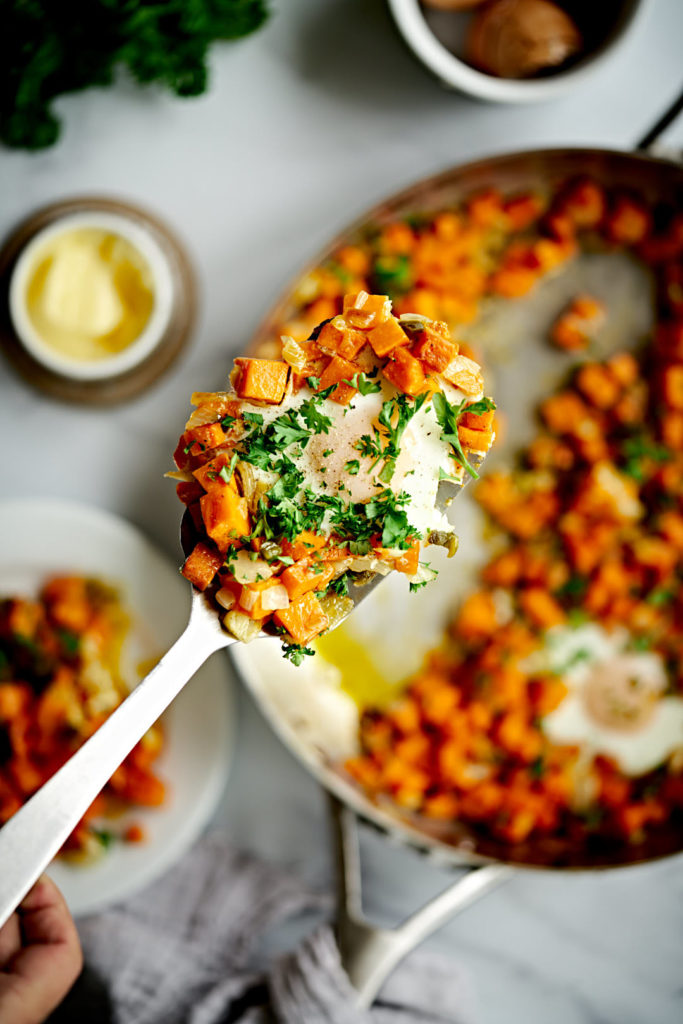 Sweet potato hash on spatula with egg and parsley.