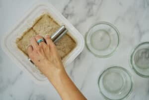 Hand cutting container of dough into four parts.