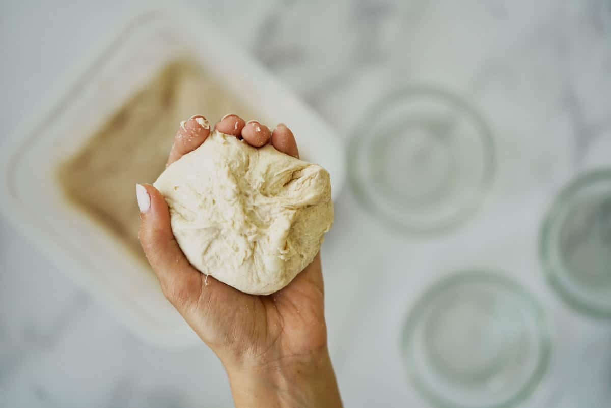 Hand holding dough that has been pinched.