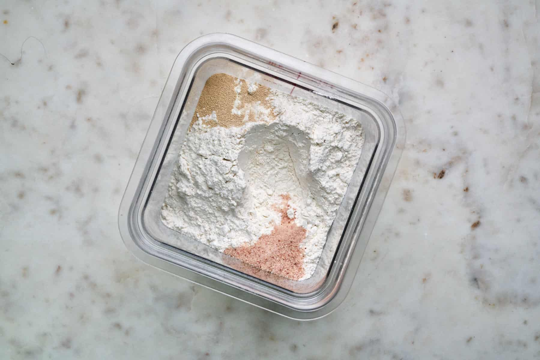 Plastic container with flour, salt, and yeast separate.