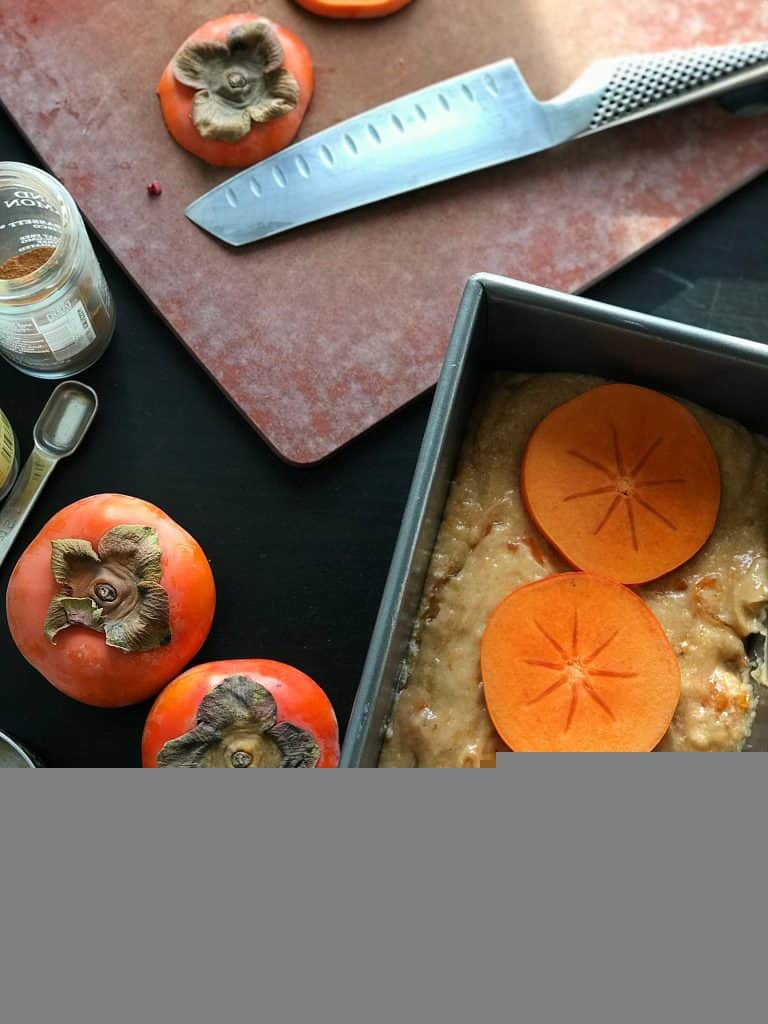 Raw bread loaf with orange fruit next to cutting board with persimmons and knife.