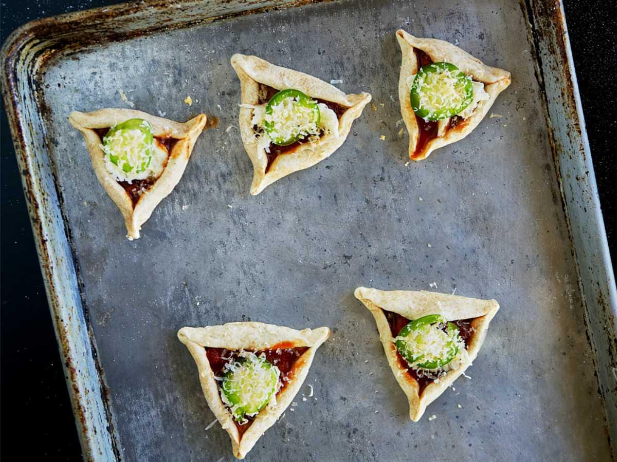 Mini triangular pizzas on a baking sheet.