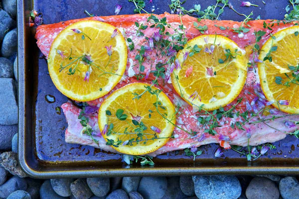 Salmon with citrus slices and herbs.