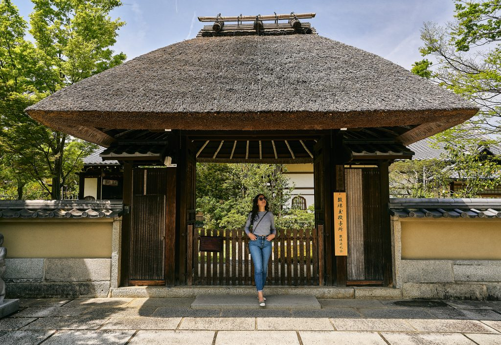 Girl standing in front of hut in Japan.