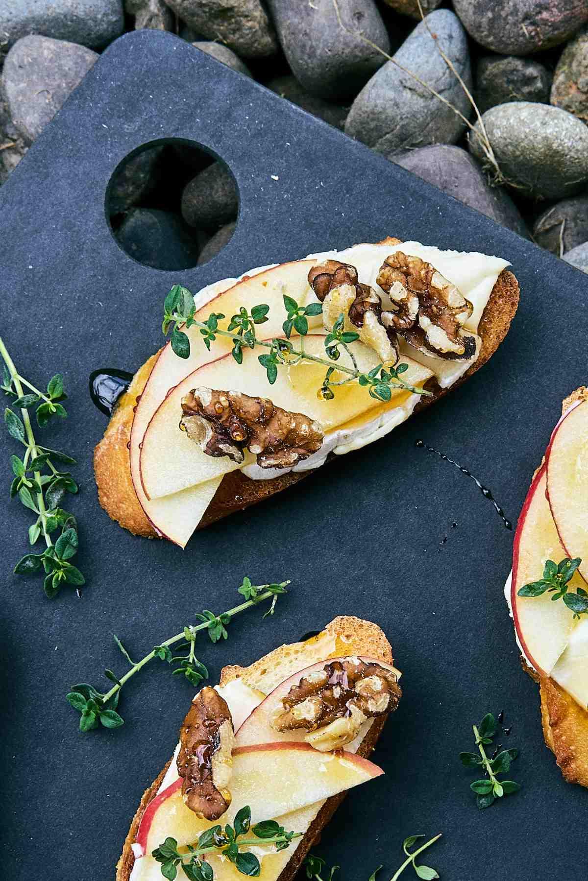 Crostini on a cutting board with fresh thyme.
