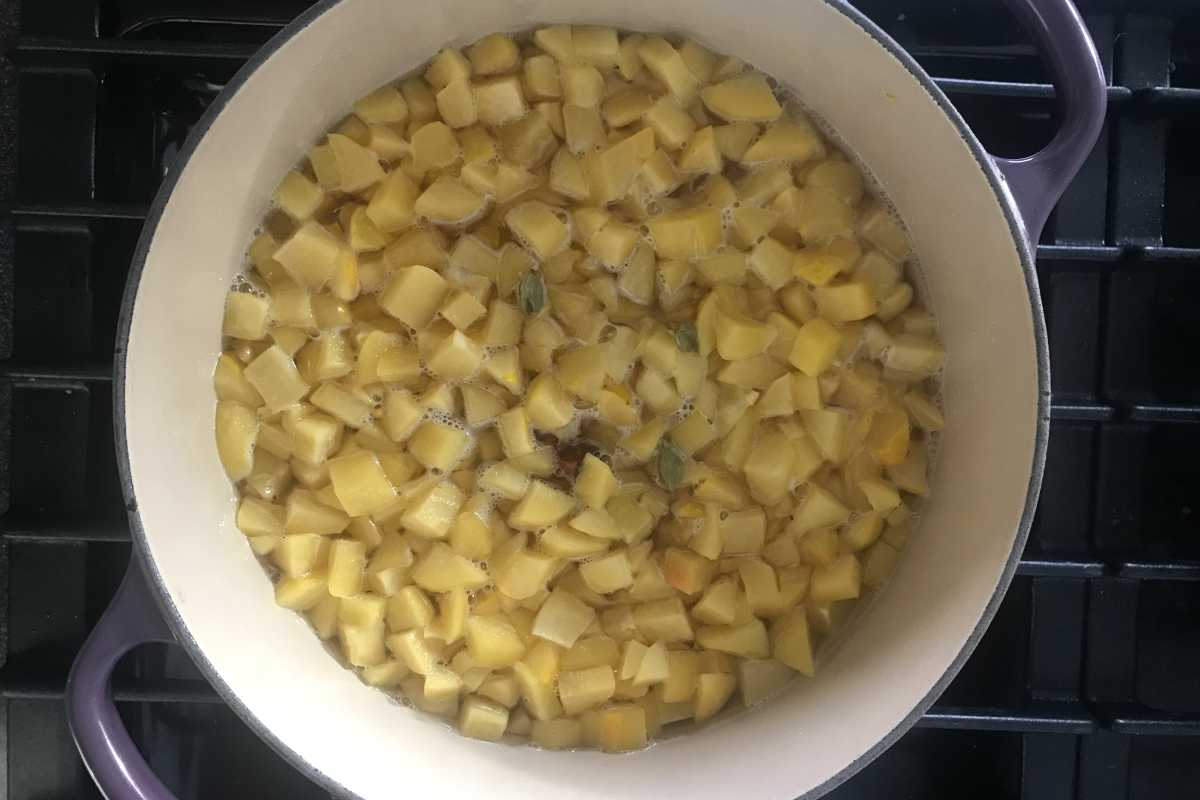 Diced yellow fruit in a pot with water.