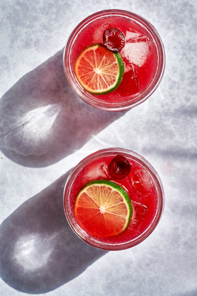 Two red cocktails with lime and cherry with shadows.