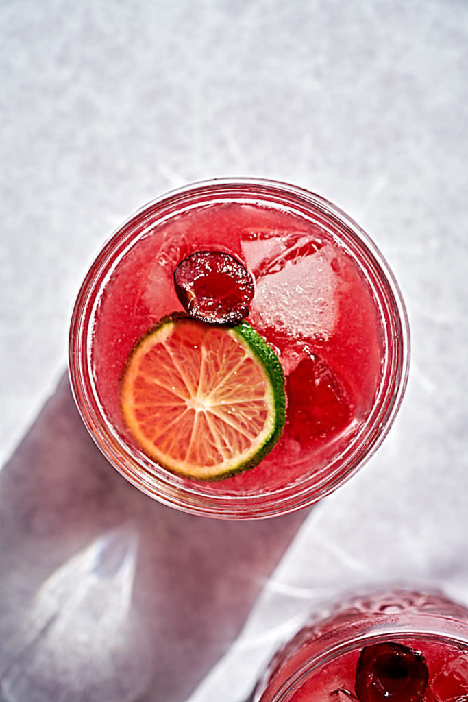 Pink cocktail with cherry and lime.