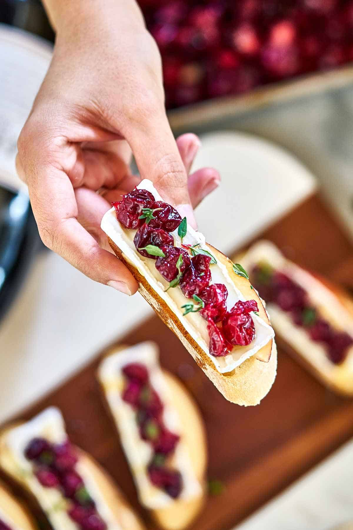 Hand holding a piece of crostini.