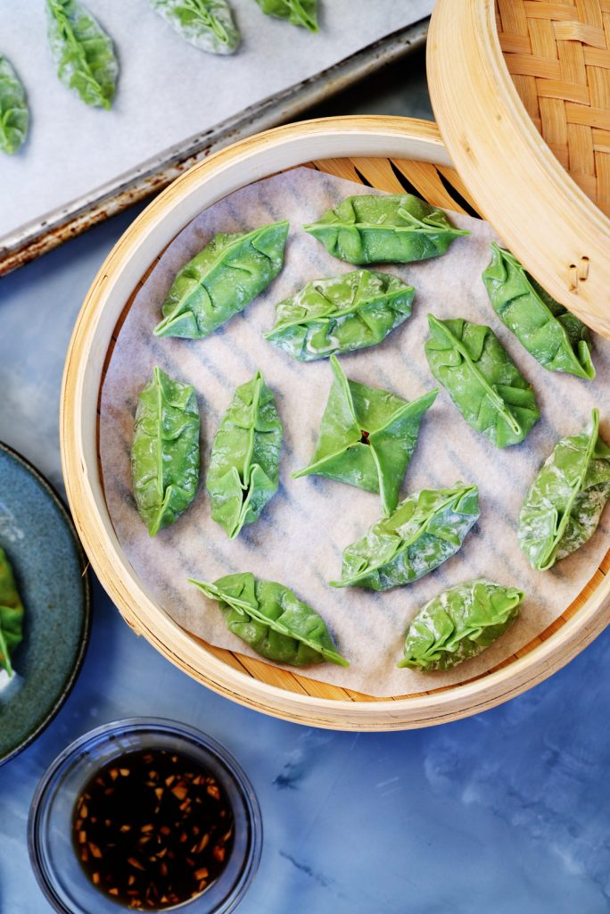 Green dumplings ready to steam in bamboo steamer.