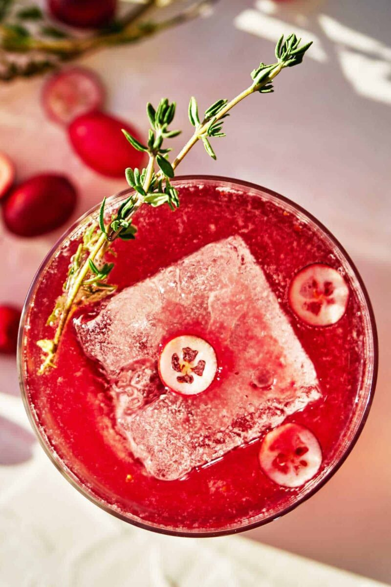 Red beverage with cranberry slices and thyme garnish.