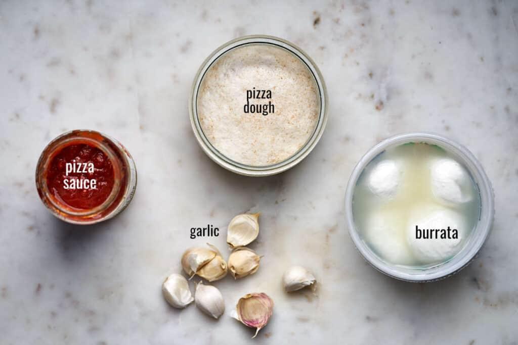 Top view of pizza sauce, dough, burrata, and garlic.