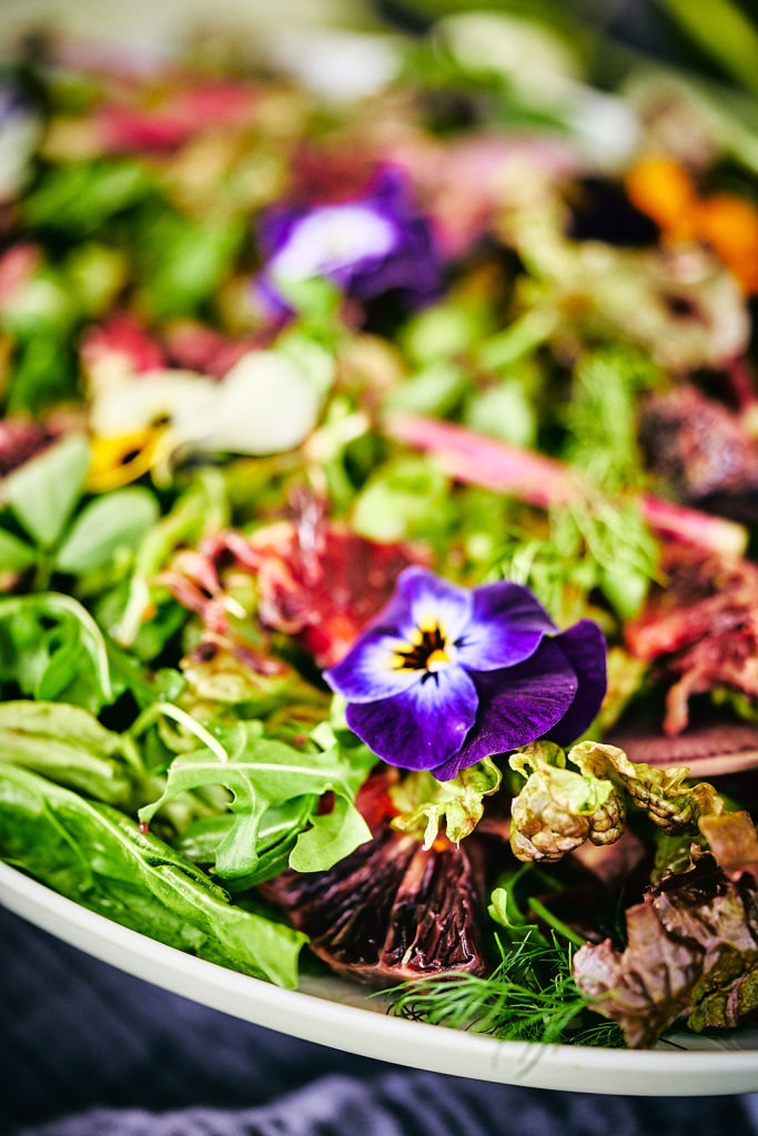 Close up of flowers and herbs on a salad.