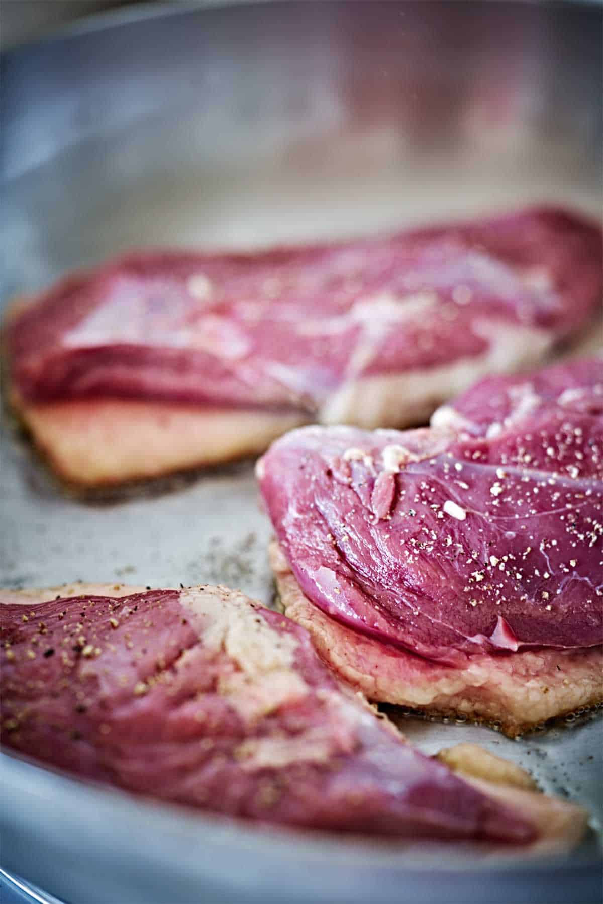 Cooking duck breasts in a pan.