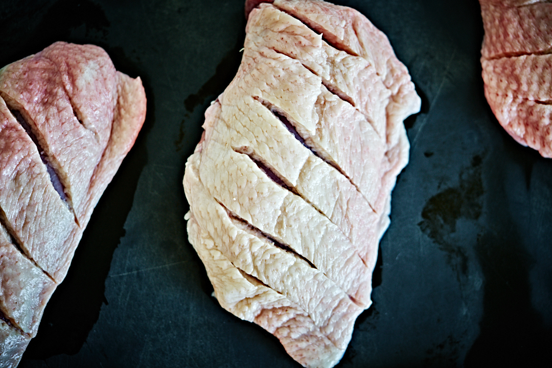 Duck breasts with scored skin.