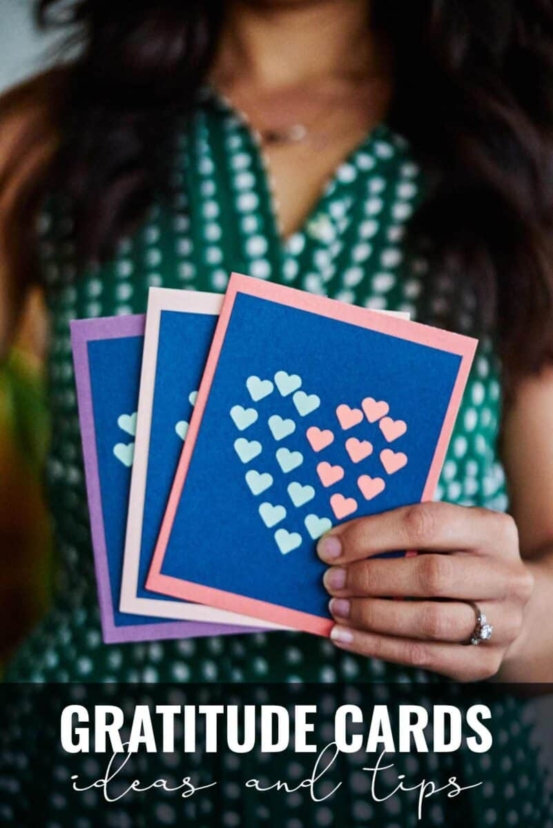 Woman holding three cards with hearts on them.