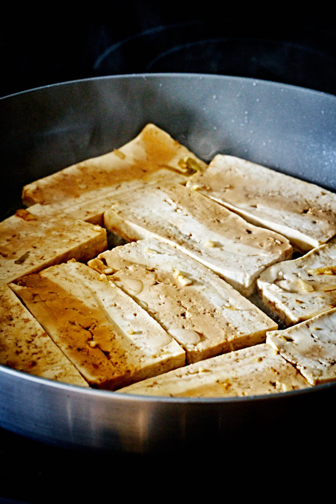 Marinated tofu cooking in a pan.