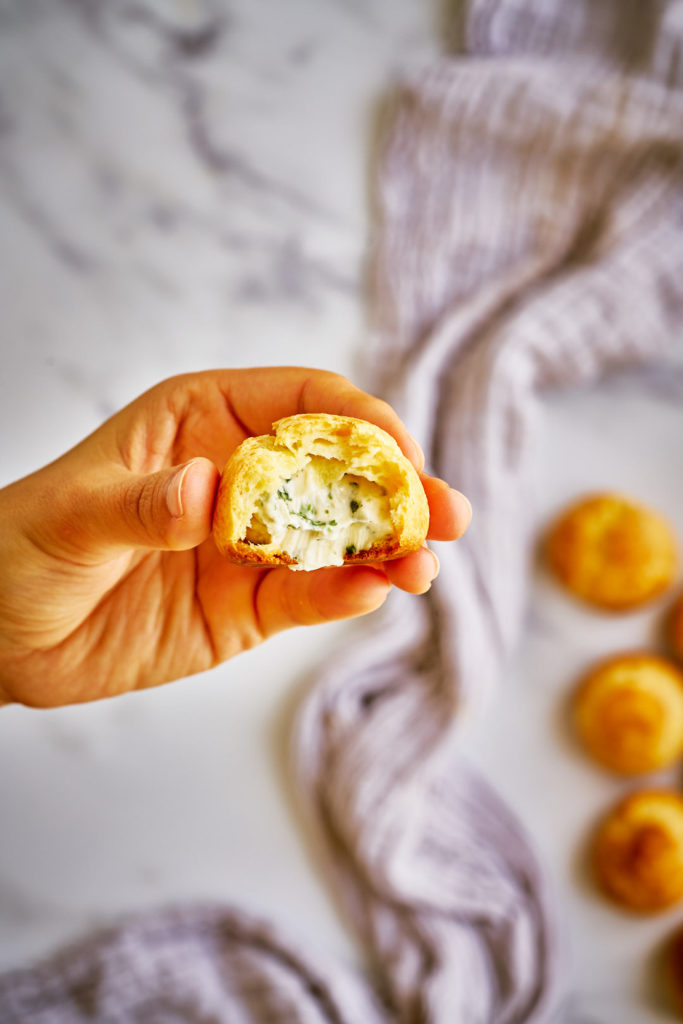 Hand holding cheese filled cream puff.