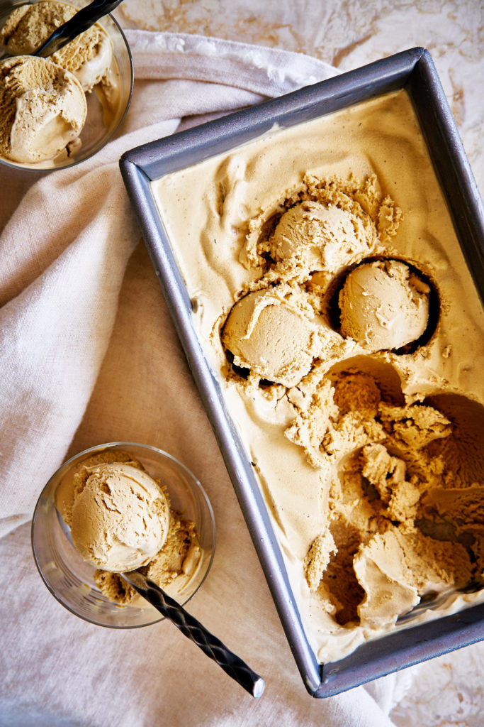 Flatlay of ice cream scooped in glass cups and bread pan