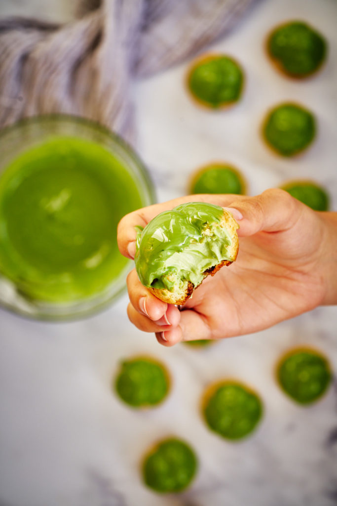Hand holding green cream puff.