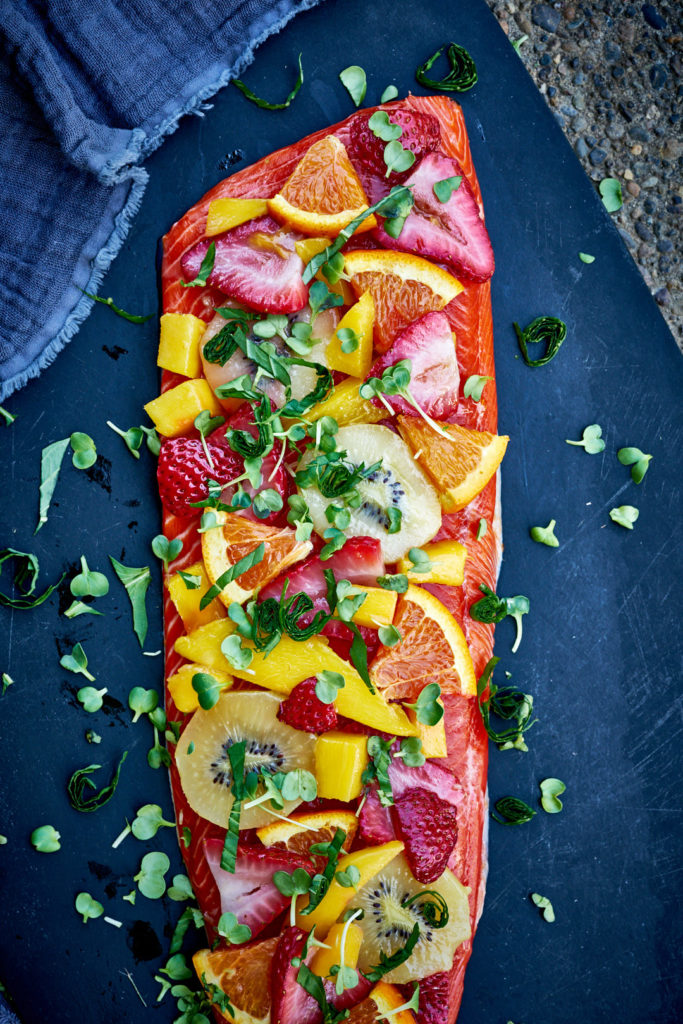 Salmon topped with summer fruit and fresh herbs on a cutting board.