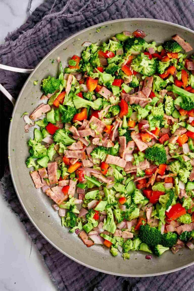 Broccoli, red pepper, and bacon in a non-stick pan.
