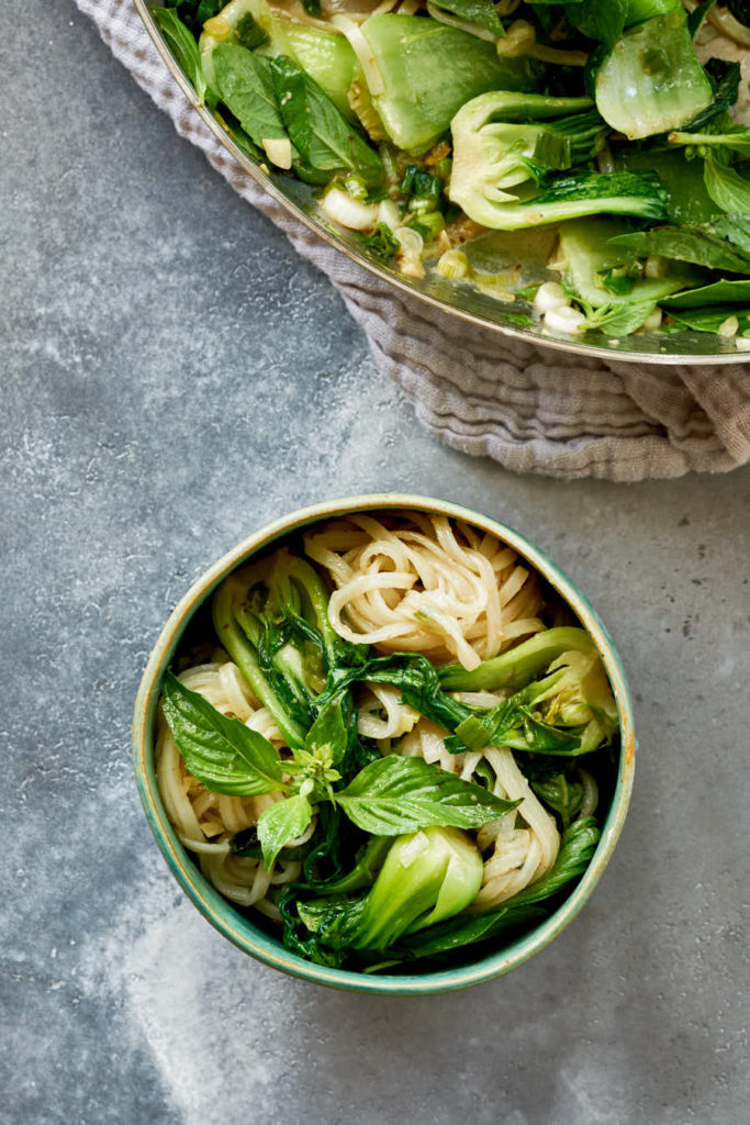 Bowl of noodles with bok choy and basil.