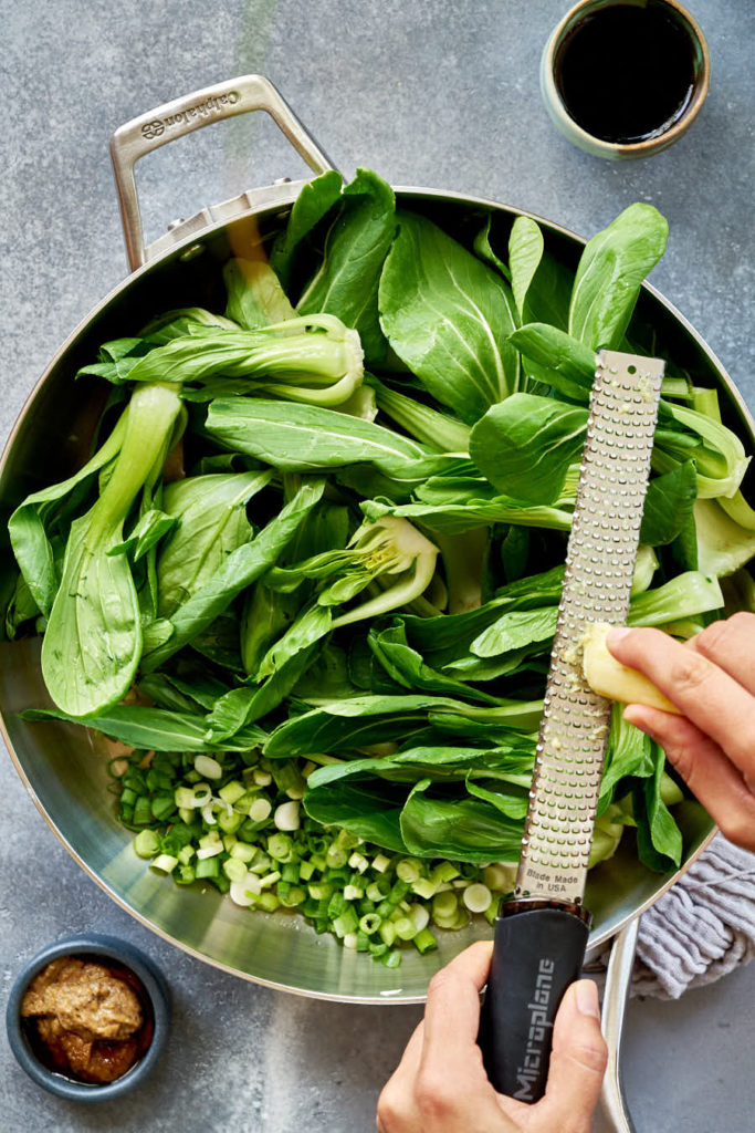 Grating ginger into fry pan filled with bok choy.