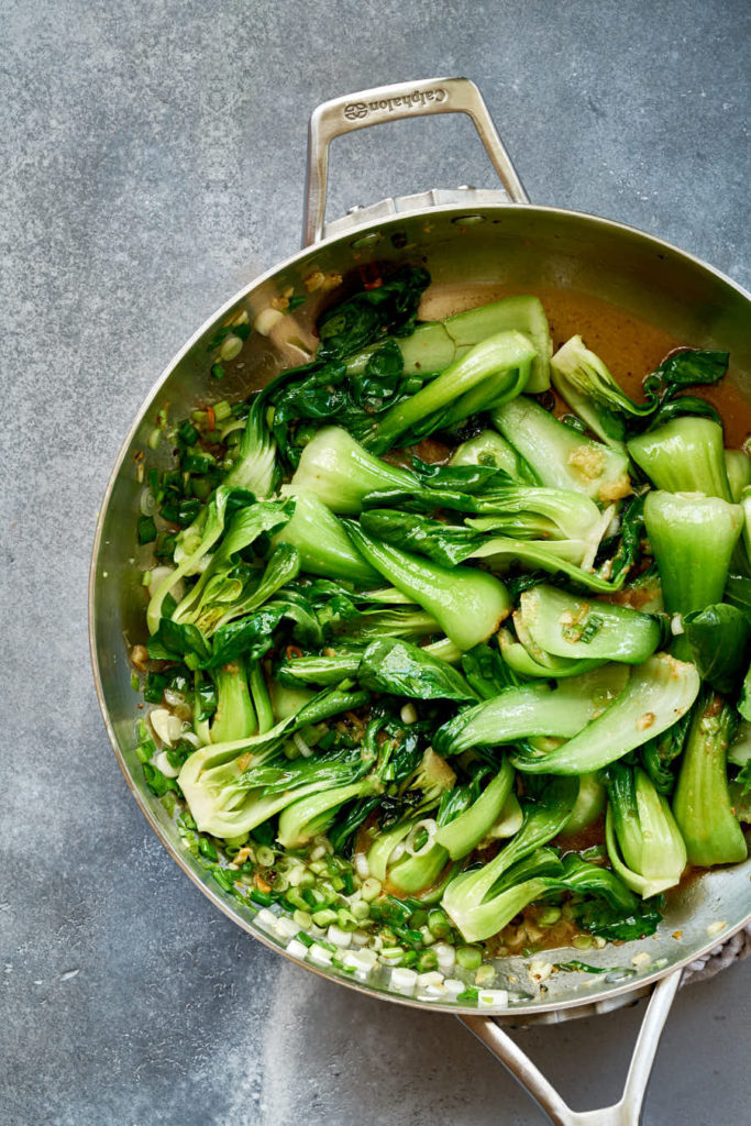 Cooked green vegetables in a fry pan.