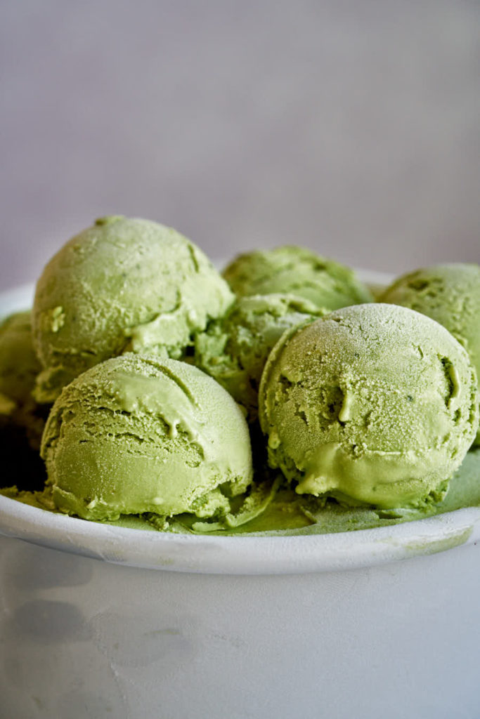 Green ice cream in metal container.