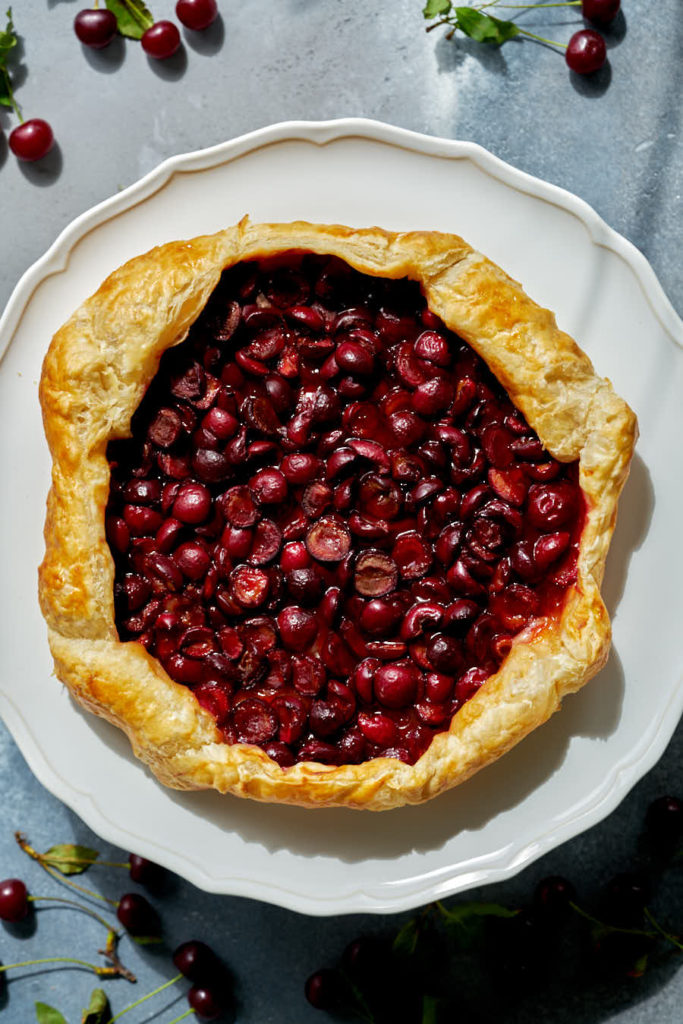 Cherry galette on a white cake stand.
