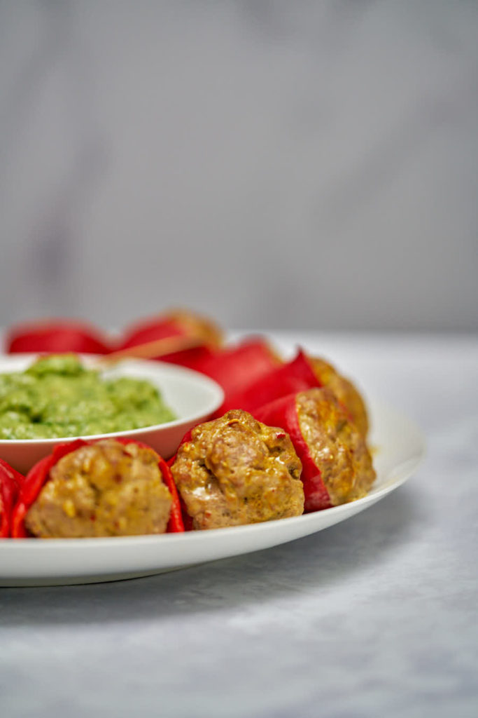 Stuffed red peppers on a white plate with green sauce.