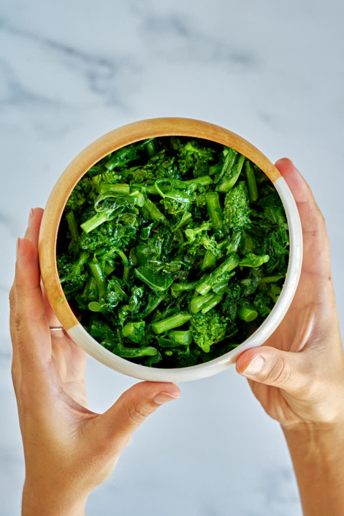 Two hands holding ceramic bowl with cooked green broccoli rabe.