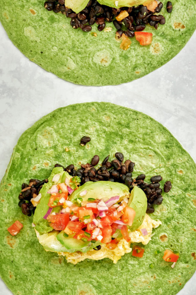 Green tortillas topped with beans, eggs, avocado, and salsa.