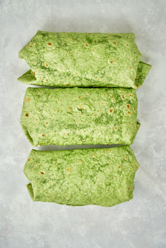 Three wrapped green burritos.