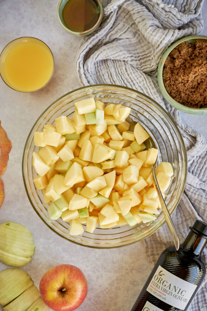 Chopped apples in a mixing bowl surrounded by ingredients.