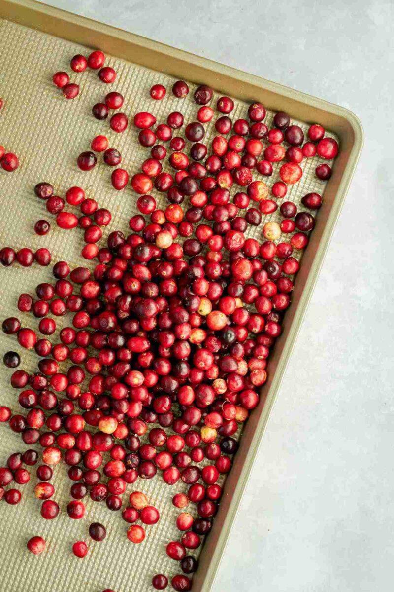 Cranberries on a gold baking sheet.