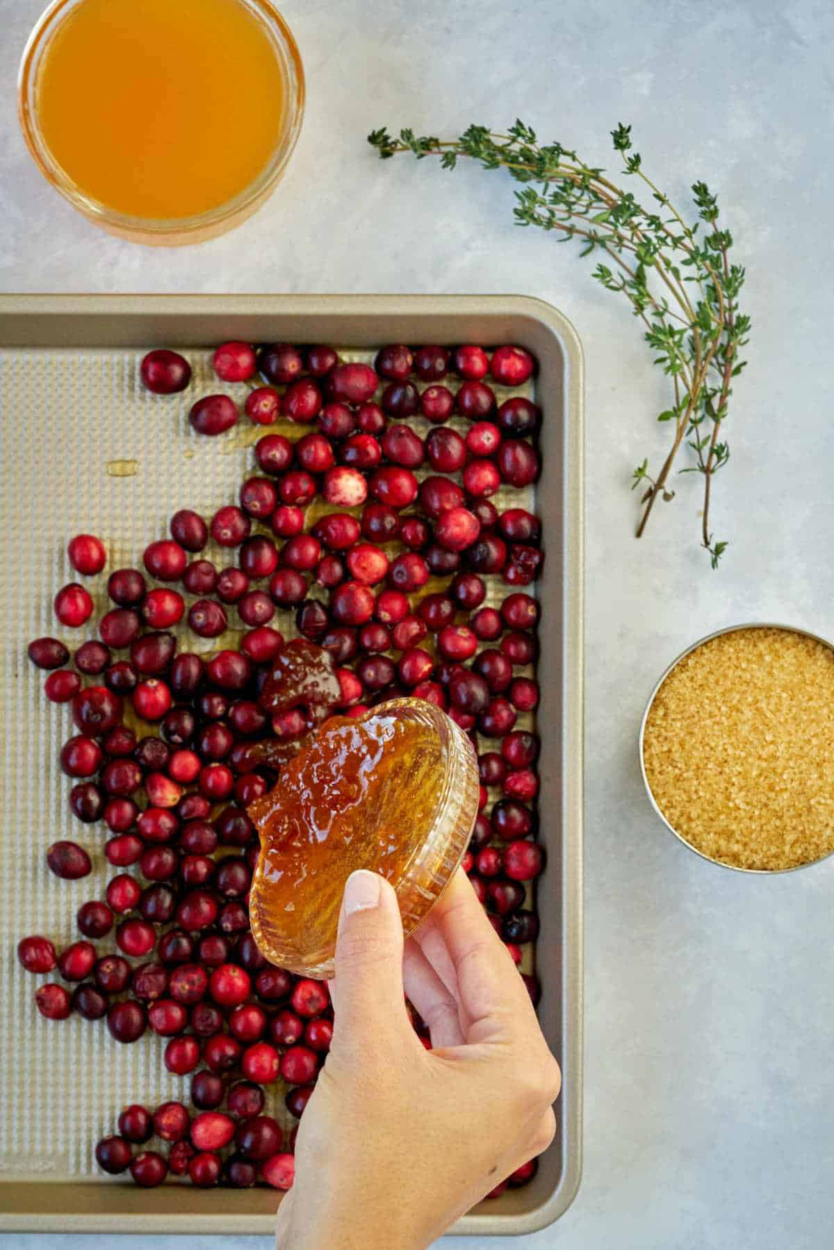 Pouring honey over cranberries in a sheet pan.