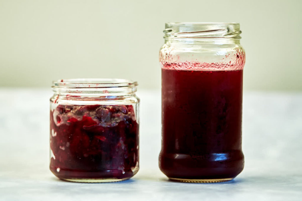 Two jars filled with burgundy liquid and fruit.