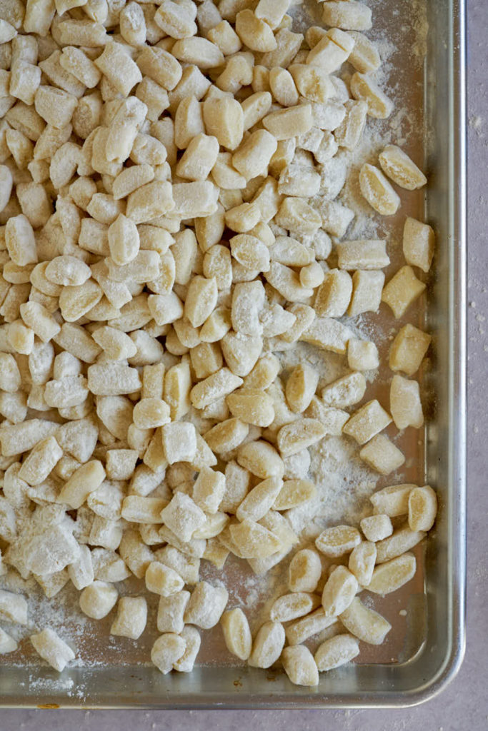 Raw gnocchi on a metal sheet pan.