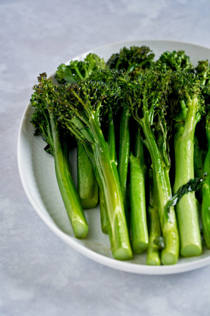 Cooked broccolini on white plate.